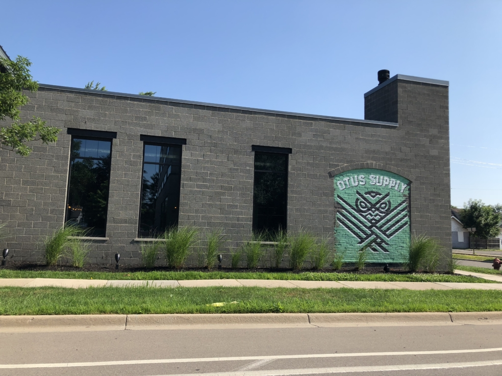 The front of the Otus Supply restaurant that faces 9 Mile Road in Ferndale, Michigan featuring grey brick and a green mural that reads Otus Supply